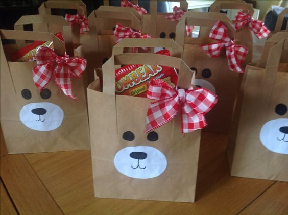 Use white lunch bags, attach a handle let kids pick faces glue them on, take home Christmas goodies.