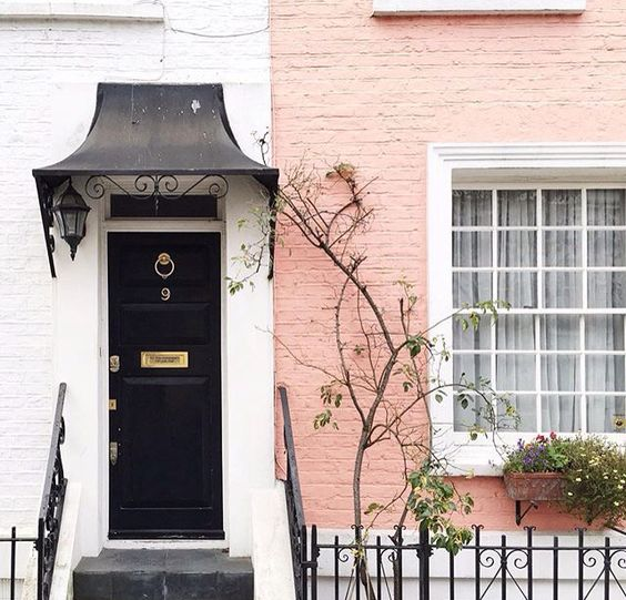 Gorgeous salmon pink painted brick on a Notting Hill home with black front door. Her Name Was Charlie.