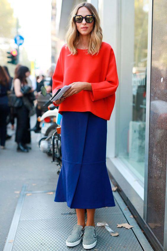 Look de inverno com saia midi azul + blusa fluida vermelha e tênis.