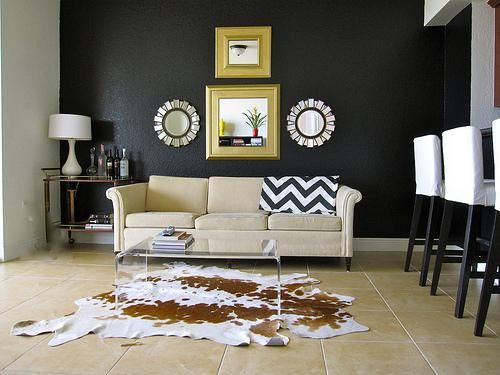Here is an example of Cowhide Rug in a living room over tile