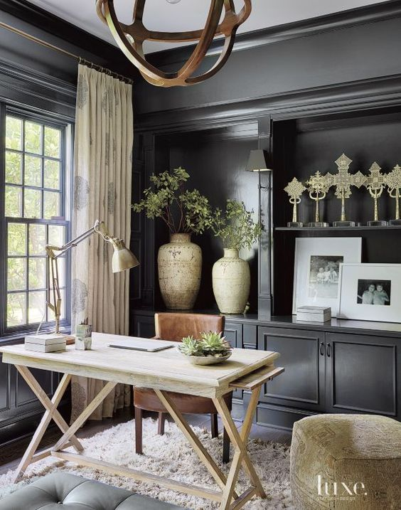An oak desk and leather chair, both from Jayson Home, enhance the library walls featuring Benjamin Moore paint, while a Moroccan rug from Stark adds texture to the eclectic space. Draperies in a fun pattern, fabricated by Elegant Custom Draperies, soften the room's masculine feel.: