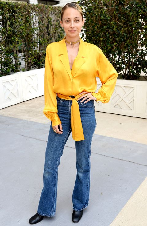 Nicole Richie in flare jeans, a yellow blouse and black boots