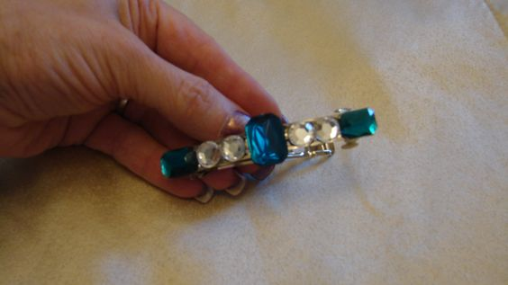 A hair barrette with teal colored and clear plastic jewels.