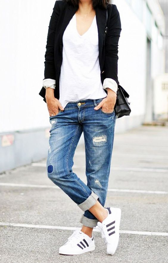 A white v-neck is paired with boyfriend jeans, sneakers, black blazer and a black bag.: