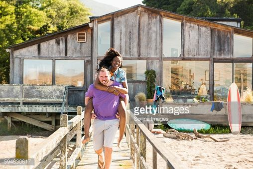 Stock Photo : Man carrying girlfriend piggyback on wooden deck