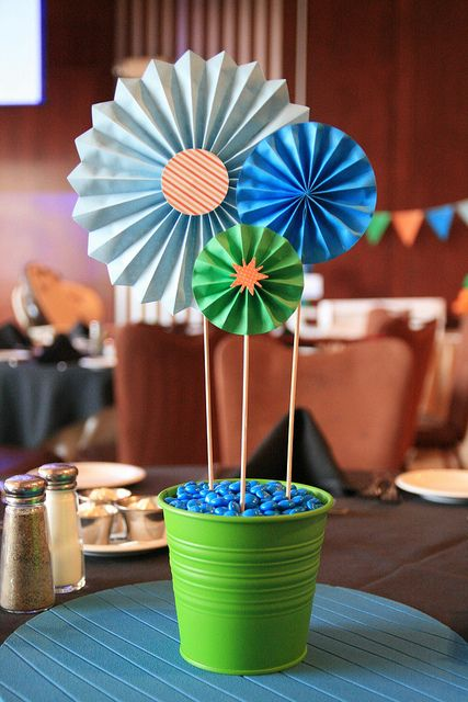 Simple & cute paper centerpieces for a robot birthday party. Buckets and charger from Ikea. Used wooden skewers as stems and stuck into styrofoam.  Covered the styromfoam w/ m's.