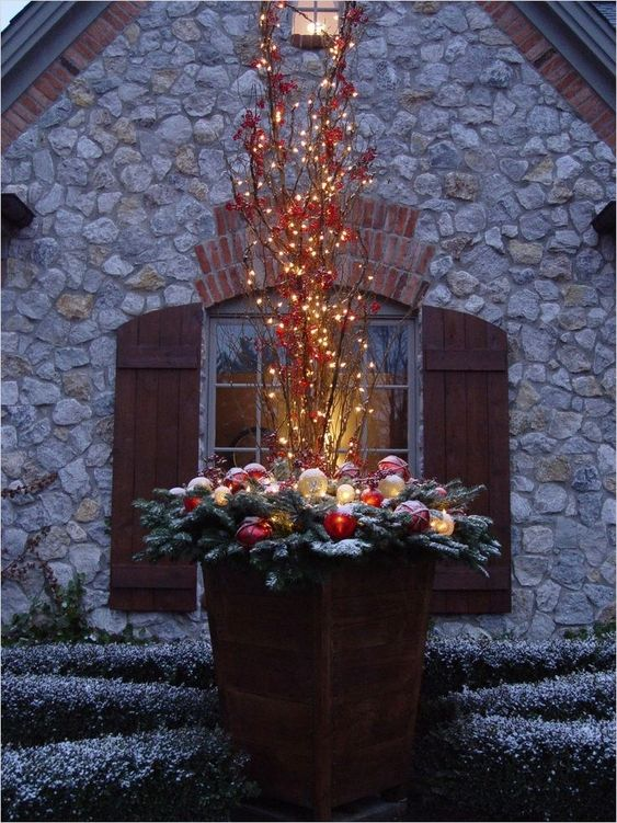 flower pot with lit-up branches and Christmas balls #christmas  #containers #planters #gardenplanters #OutdoorLighting #backyardLighting #outdoorLights #christmasLights