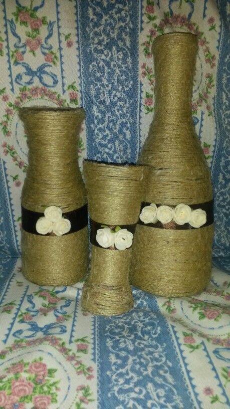 Complementi d'arredo... bottiglie rivestite con spago e decorate con nastro marrone e fiori color crema