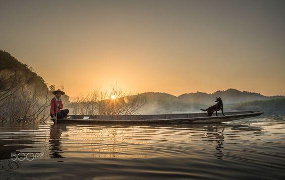 Silueta del pescador y del perro en barco por SIRISAK BOAKAEW en 500px