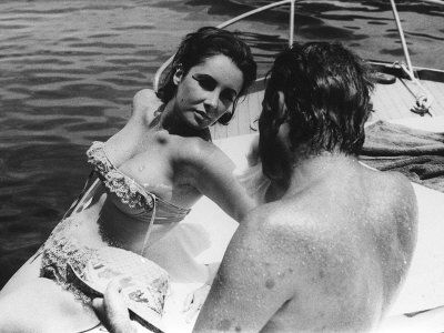 ELIZABETH TAYLOR with RICHARD BURTON on a boat  in Italy in 1963 during the filming of Cleopatra when their affair had already begun  (Photographic Print - AllPosters.co.uk)