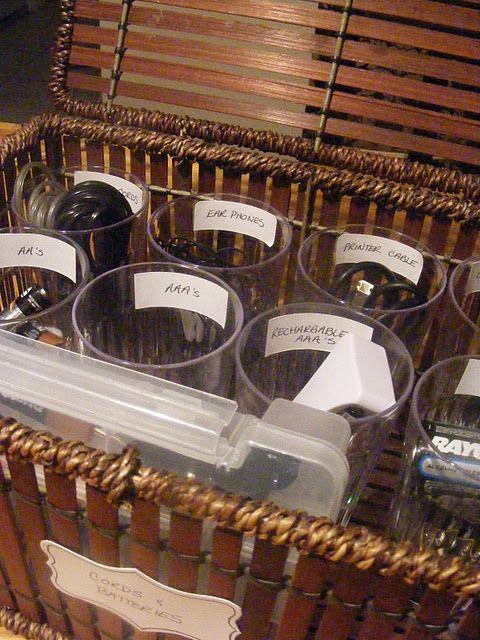Para organizar fios e baterias, use copos com etiquetas e coloque-os dentro de uma cesta ou caixa!