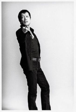 全身黒い衣装を着て指をさしている矢沢永吉の画像