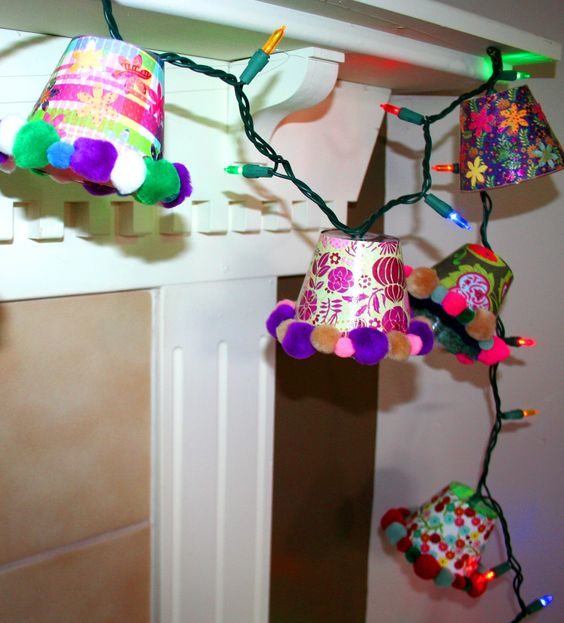 Twinkle Light Shades - Made from 16ct. dollar store clear plastic tumblers with double sided scrapbook paper mod podged to outside, sealed with several additional coats of Mod Podge on top and pom poms hot glued to rims.  Idea taken from a pin from the diycraftstomake blog.