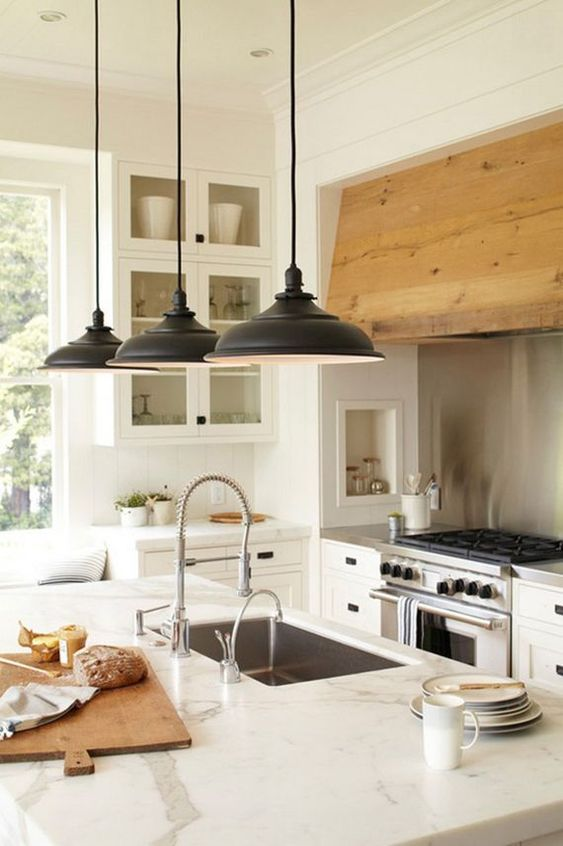 Classic white modern farmhouse kitchen with white cabinets, knotty wood range hood, stainless steel appliances, dark hardware, calacatta marble counter, wood cutting board, glass front cabinets. #modernfarmhouse #kitchen #rangehood #whitekitchen