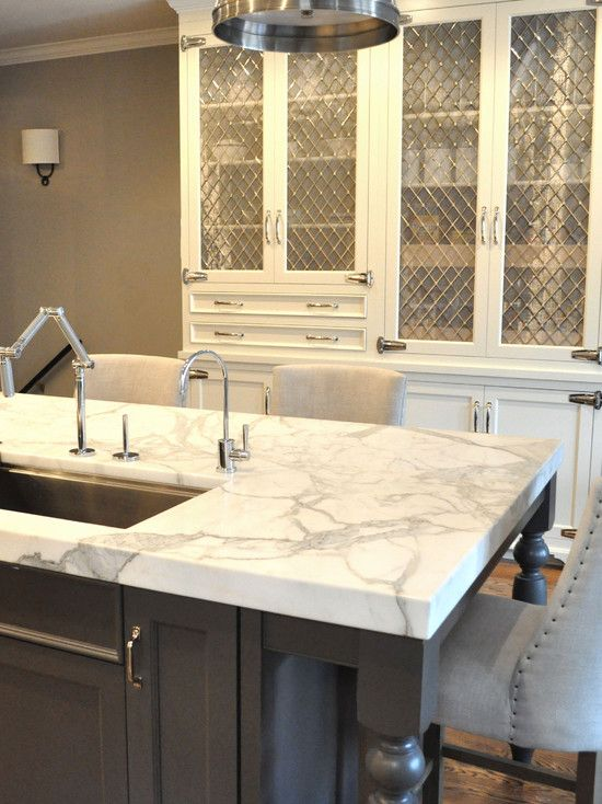 Kitchen Lab  Mother of Pearl Quartzite countertops and Sandy Chapman Single Sloane Street Shop Light with Metal Shade in Antique Nickel. Gray island with prep sink and lRestoration Hardware 1940s French Upholstered Barrelback Barstools. Perimeter cabinetry in white with leaded glass fronts.