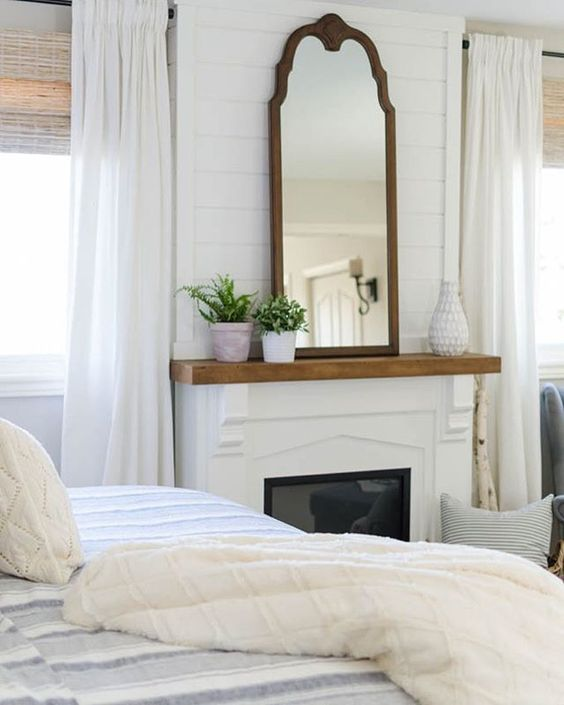 French Country decor in a bedroom with fireplace topped with elegant mirror. The white bedroom has shiplap above fireplace, natural shades, and striped bed linens. #frenchcountry #whitedecor #interiordesign #decorideas #farmhousestyle #farmhousedecor #modernfarmhouse #shiplap