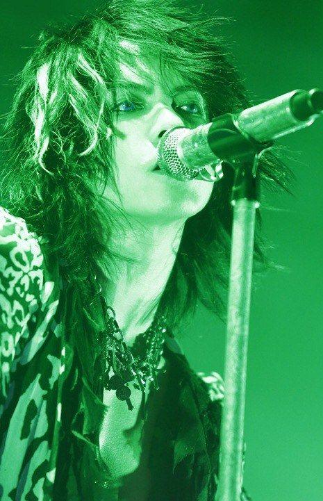 セミロングのパーマスタイルで歌っているL'Arc〜en〜Ciel・hydeの画像