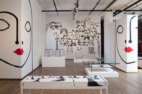 Ralph Pucci Showroom walls in white with black and red modern art murals....love it.