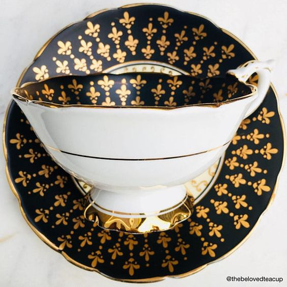 Incredibly flashy black and gold Royal Stafford antique tea cup and saucer featuring handpainted fleur de lis details and a beautiful pink rose centre motif. Set is in good antique condition, there is some slight fading to the gold gilding and a short hairline underneath the handle,