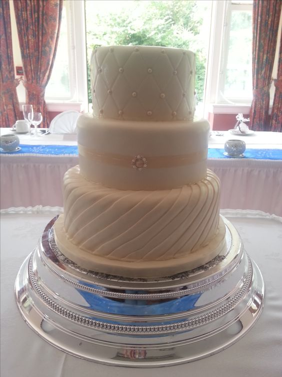 Round 3 tied wedding cake with drape, quilting and brooch