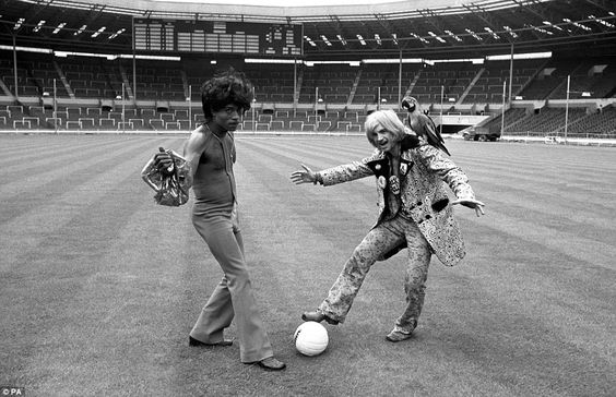 Little Richard, the American rock singer, is seen with a football for a change. He and 'screaming' Lord Sutch, who is carrying a parrot at the Stadium in Wembley