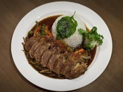 Pad Gar Pow Duck is a large entree of thick, juicy and decadent slices of duck breast fanned on a plate with garlic chili sauce, a medley of sauteed vegetables and white rice.