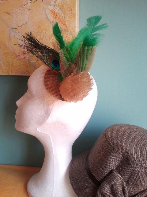 tocado realizado con base de sinamae dorada crin plisado del mismo color rematado con plumas de pato y pavo real