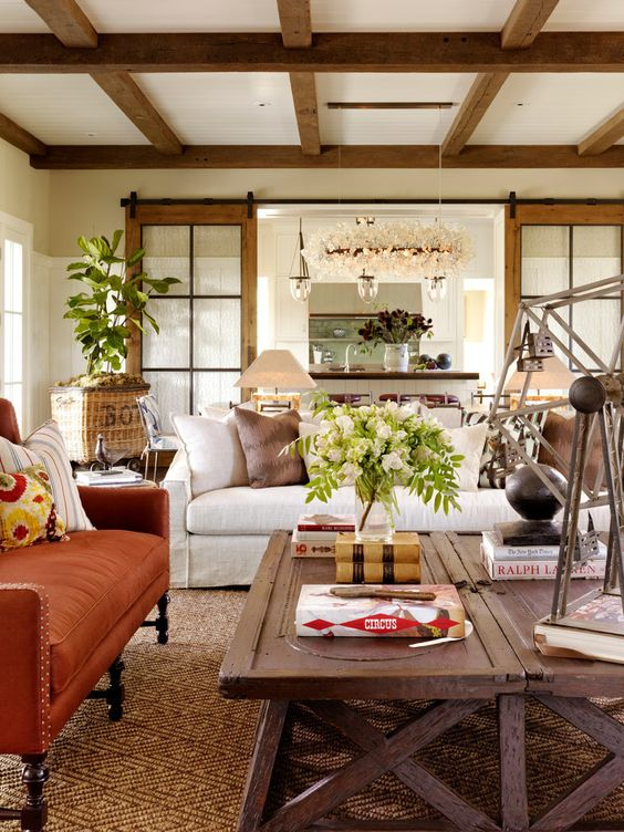 A white living room with wood beams, rustic furnishings, white sofa, orange velvet settee