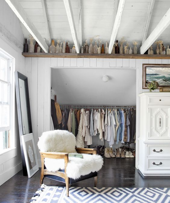 Leanne Ford's closet with white painted paneling, vintage chair draped with a sheepskin rug, and a shelf near the rafters lined with collected vintage bottles. Closet doors have been removed, and a Navajo black and white rug add charm. #LeanneFord #vintagestyle #closetdecor