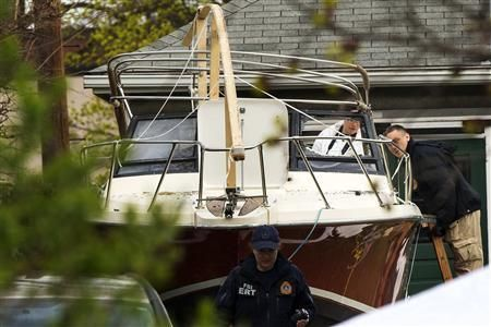 Members of the FBI Evidence Recovery Team inspect the boat where Boston Marathon bombing suspect Dzhokhar Tsarnaev was hiding at 67 Franklin St. in Watertown, Massachusetts, April 20, 2013. REUTERS-Lucas Jackson