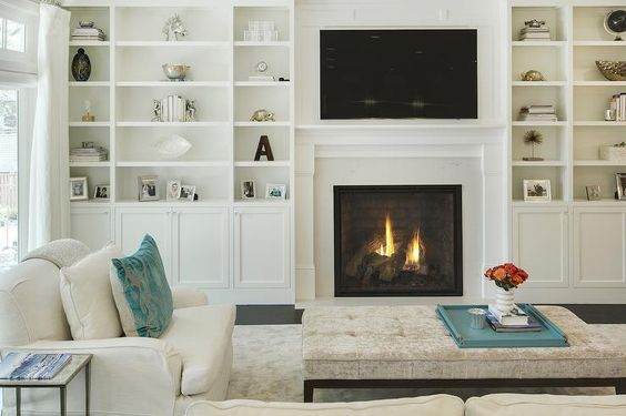 Chic transitional living room features a sleek white fireplace and a flatscreen tv flanked by for Floor to ceiling cabinets for living room
