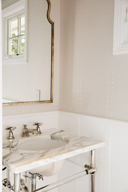Powder room features upper walls clad in gray wallpaper and lower walls clad in white paneling lined with a polished nickel and glass washstand topped with statuary marble under a metal vanity mirror.