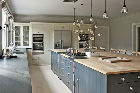 Dark island light wood wide plank floors and light floor to ceiling cupboards