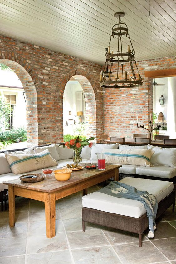 A Sunbrella-covered sectional and ottoman, plus a nearby dining table that seats eight, make this covered porch ideal for outdoor entertaining.    Steal this Idea: A high coffee table allows a seating area to pinch-hit for dining  Source Guide Pillows: made with Sunbrella Fabric by DyAnne Cavell and Carol Vorhoff