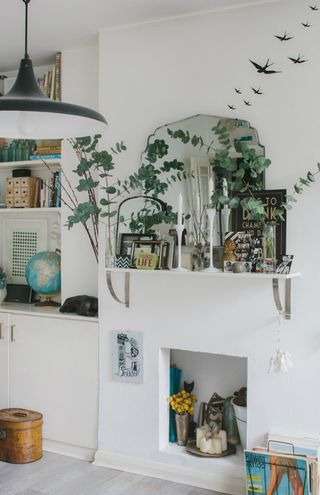 A vintage home simple rustic shelf as a mantle filled with plants