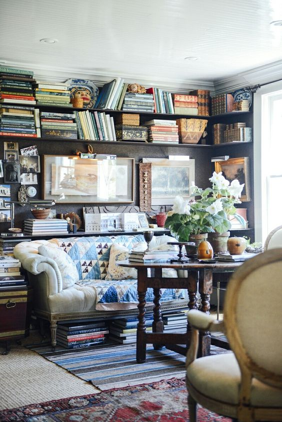 A cozy library/ family room with dark panelled walls full of books and art.
