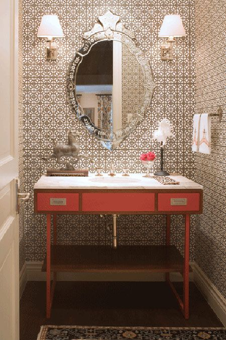 vintage washroom: geometric wallpaper, large oval silver embellished mirror with twin set lights, wood and pink accented wash basin table