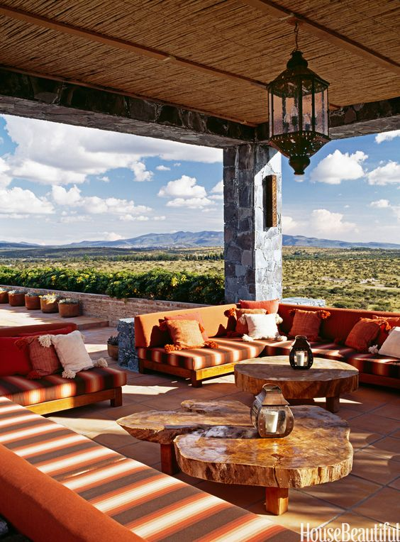 In John Houshmand's Mexican hacienda, mesquite banquettes upholstered in Sunbrella wrap around the upstairs loggia, which has a spectacular view. The tables, made from mesquite slabs, were highway finds.   - HouseBeautiful.com