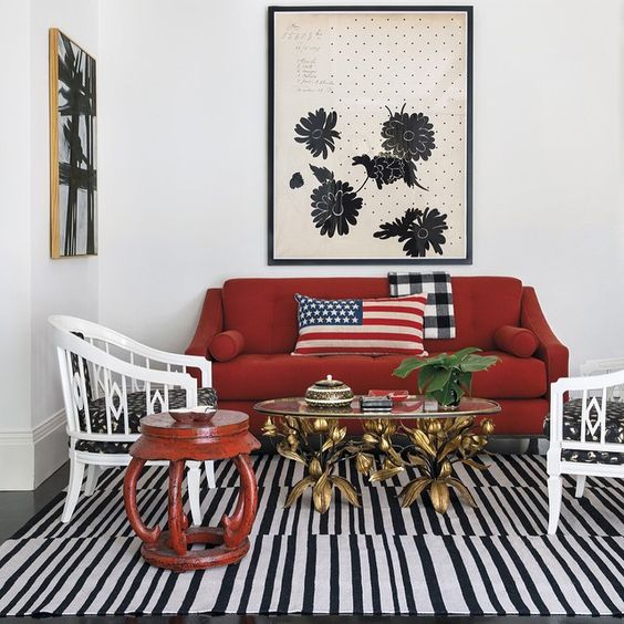 Red, white and blue in an eclectic sitting area by Burnham Design. Red loveseat with American flag pillow. #americanflag #homedecor #redandwhite