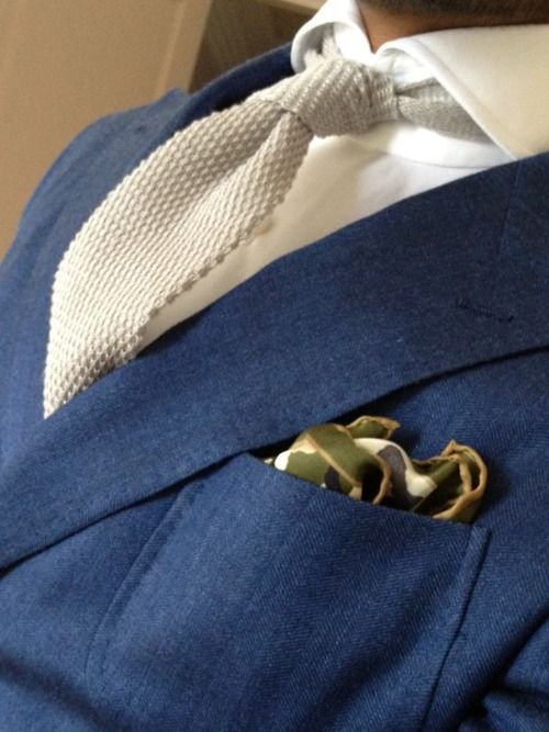 white knit tie adds texture atop a white shirt, giving contrast to a medium-dark blue suit jacket with pocket square