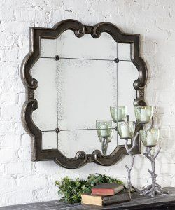 prisca distressed wall mirror large, distressed silver leaf finish wood frame with black undertones. The etched, antiqued mirror has four matching rosettes