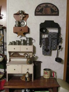 """This is one small wall in my kitchen. The little white hutch was made by my Great Grandfather for my Mom in 1927! The things hanging on the little rack on the right with the towels are called Betty Lamps. The one on the right bottom is a reproduction. The one on the left is a double tin one from the 1700's. The pewter """"mugs"""" on the small hutch are English and intended for measuring (mid 1800's)."""