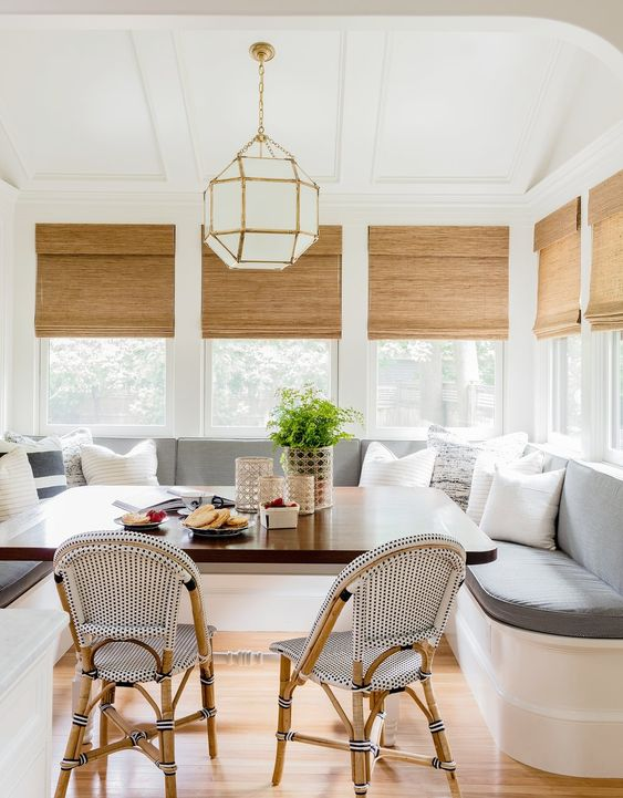 The perfect breakfast nook built-in with rattan seating + roman shades + modern pendant | Hudson Interior Designs