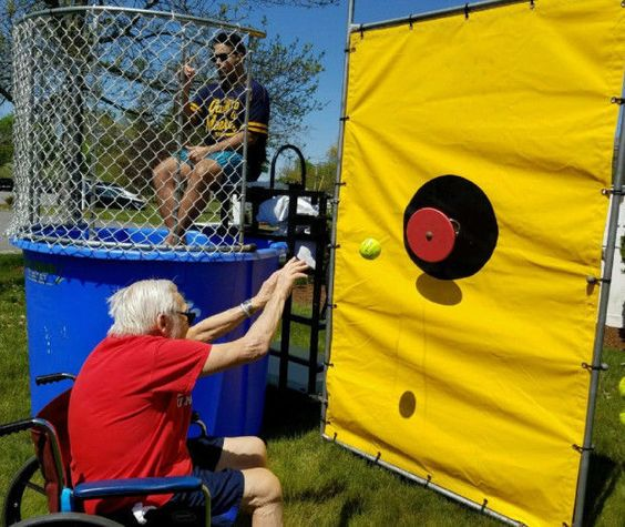 """Samantha Bennett submitted this photo of Wingate at Norton resident Ed Tumavicus taking """"his best shot at Wingate at Norton Food Service Director Tiago Gomes at the dunk tank during the community's spring carnival event."""" (Submitted photo)"""