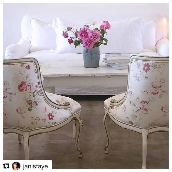 Shabby chic living room with floral upholstered vintage chairs, white denim sofa, and rustic white coffee table with bright pink flowers. #rachelashwell #shabbychic #livingroom #pink