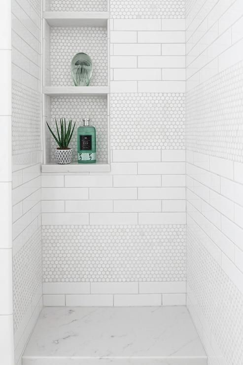 White hexagon shower tiles in a transitional walk-in shower featuring white stacked wall tiles in niches with marble slab flooring.