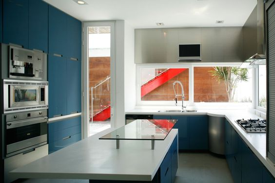 Minimalist Industrial inerior design with blue acccents.  White Kitchen Table Surface With Blue Shelf And Glazed Accents In Kitchen