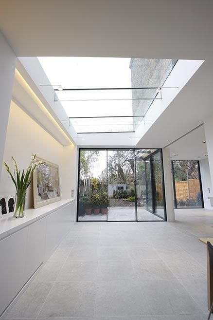 The versatile glass extension on this traditional home uses a ...