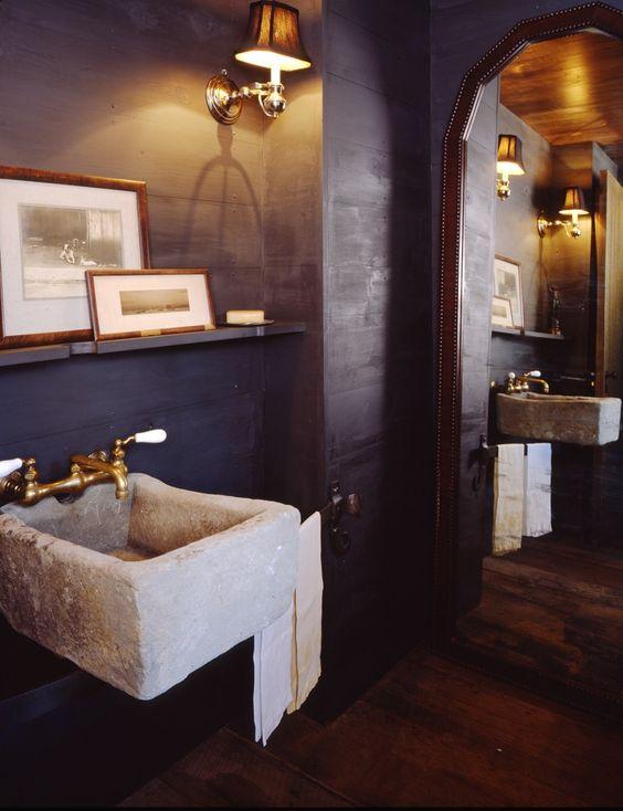 reforma baño con pila de piedra como lavabo, paredes color carbón, espejo gran formato, suelo parquet.