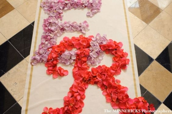 Instead of an aisle runner, use petals to spell out your wedding initials. Photo: The Minnericks.